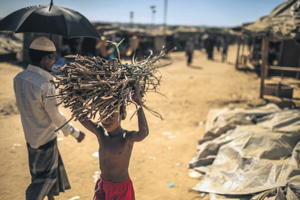 A young Rohingya refugee carries firewood as he walks through the Kutupalong refugee camp, Cox's Bazar, Bangladesh, Dec. 4.
