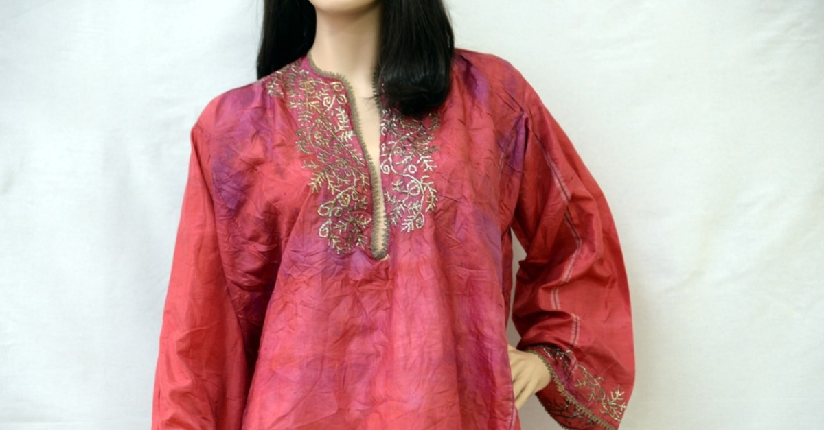 The shirt is made of red silk featuring hand embroidery.