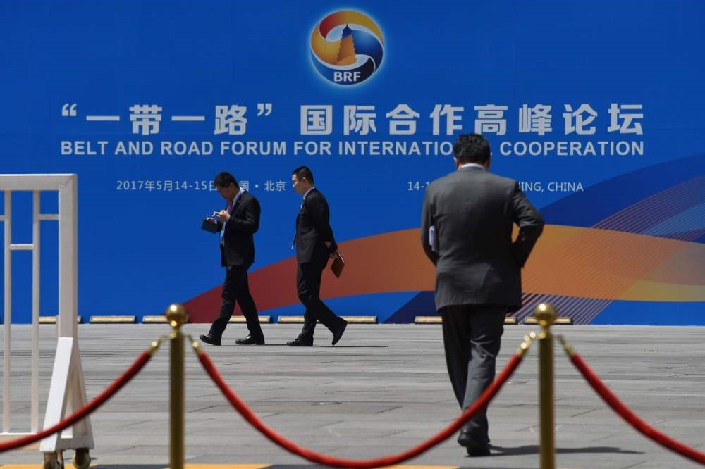 People walk past a billboard for the Belt and Road Forum for International Cooperation at the venue for the forum in Beijing on May 11, 2017. (AFP Photo)