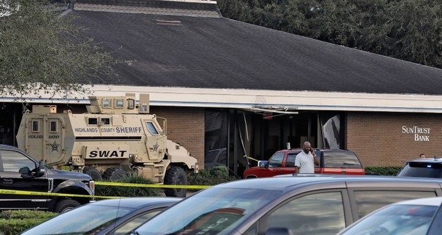A Highlands County Sheriff's SWAT vehicle is stationed out in front of a SunTrust Bank branch, Wednesday, Jan. 23, 2019, in Sebring, Fla., where authorities say five people were shot and killed. (AP Photo)
