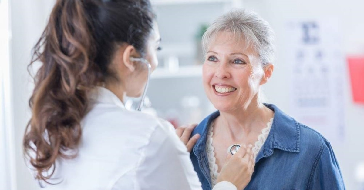 An elderly woman is examined by a doctor.