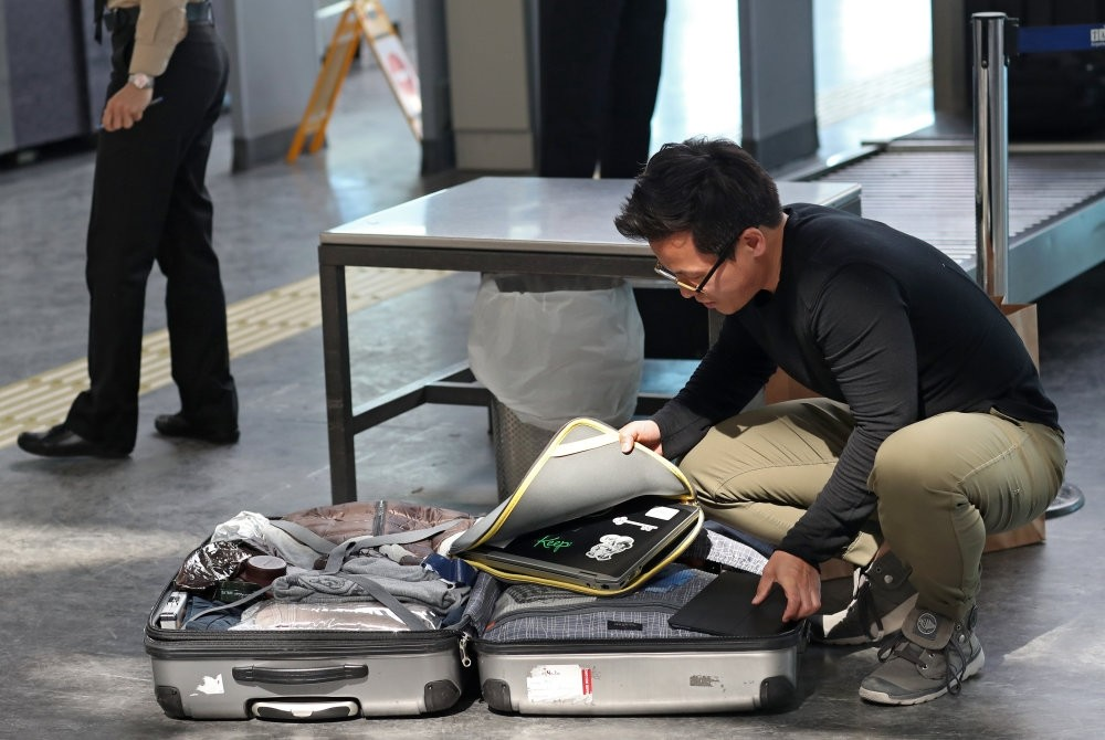 Passengers open their luggage and show their electronics at a security point at Atatu00fcrk International Airport, Istanbul.