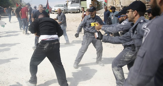 An Israeli policeman tasers a Palestinian activist in the Bedouin village of Khan al-Ahmar, West Bank, Oct. 17.