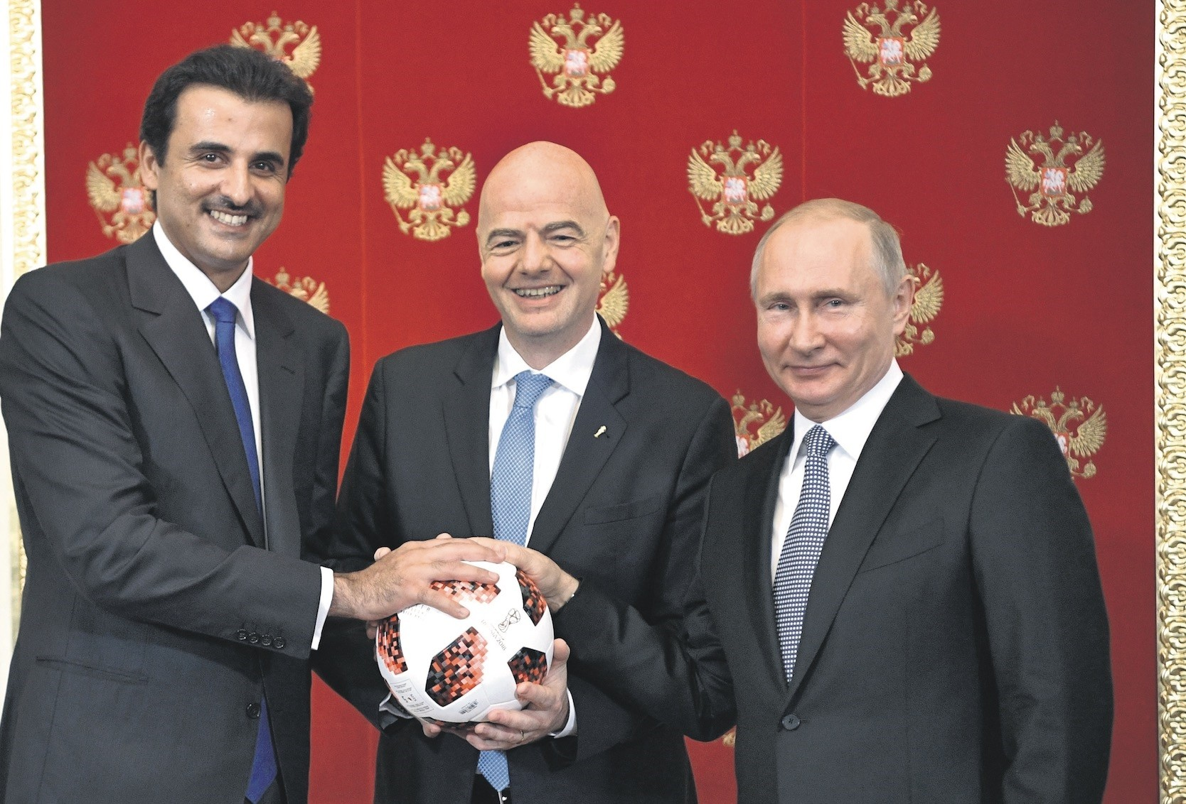 The Emir of Qatar Sheikh Tamim bin Hamad al-Thani (L), FIFA President Gianni Infantino and Russian President Vladimir Putin pose for a photo during their meeting in the Kremlin in Moscow, July 15.
