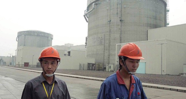 Workers walk past a part of the Qinshan No. 2 Nuclear Power Plant, China's first self-designed and self-built national commercial nuclear power plant in Qinshan, about 125 kilometers southwest of Shanghai, China.