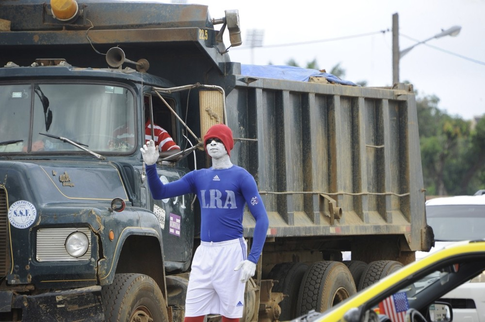 A young Liberian man stands in the sweltering heat for hours, painted head to toe in the colours of the national tax authority, at a traffic junctions.