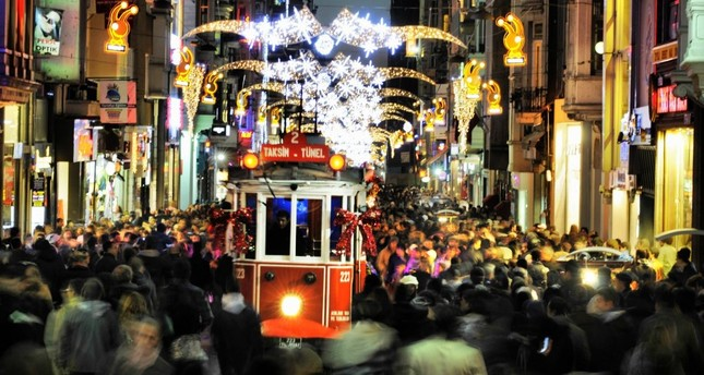 A tramway passes by as people walk on the crowded İstiklal street in Istanbul.