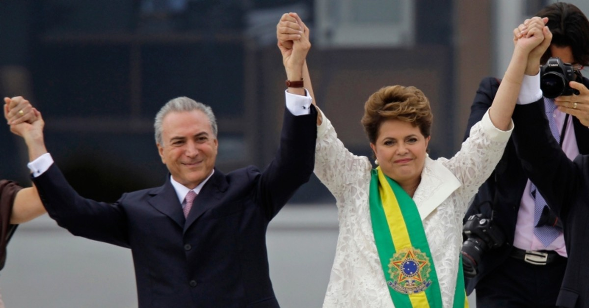 In this Jan. 1, 2011 file photo, Brazil's President Dilma Rousseff, right, raises arms with her Vice President Michel Temer at the end of her swearing-in ceremony at Planalto Palace in Brasilia, Brazil. (AP Photo)