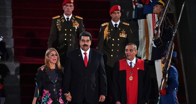 Venezuela's President Nicolas Maduro (C) walks flanked by First Lady Cilia Flores and the president of the  Supreme Court of Justice (TSJ) Maikel Moreno (R) upon arrival for the inauguration ceremony of his second mandate (AFP Photo)