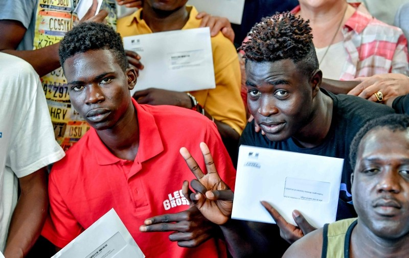 Sudanese migrants arrived in France with the rescue ship Aquarius pose with their refugee identity certificates after a ceremony at the City Hall in Llille, northern France, on August 3, 2018. (AFP Photo)