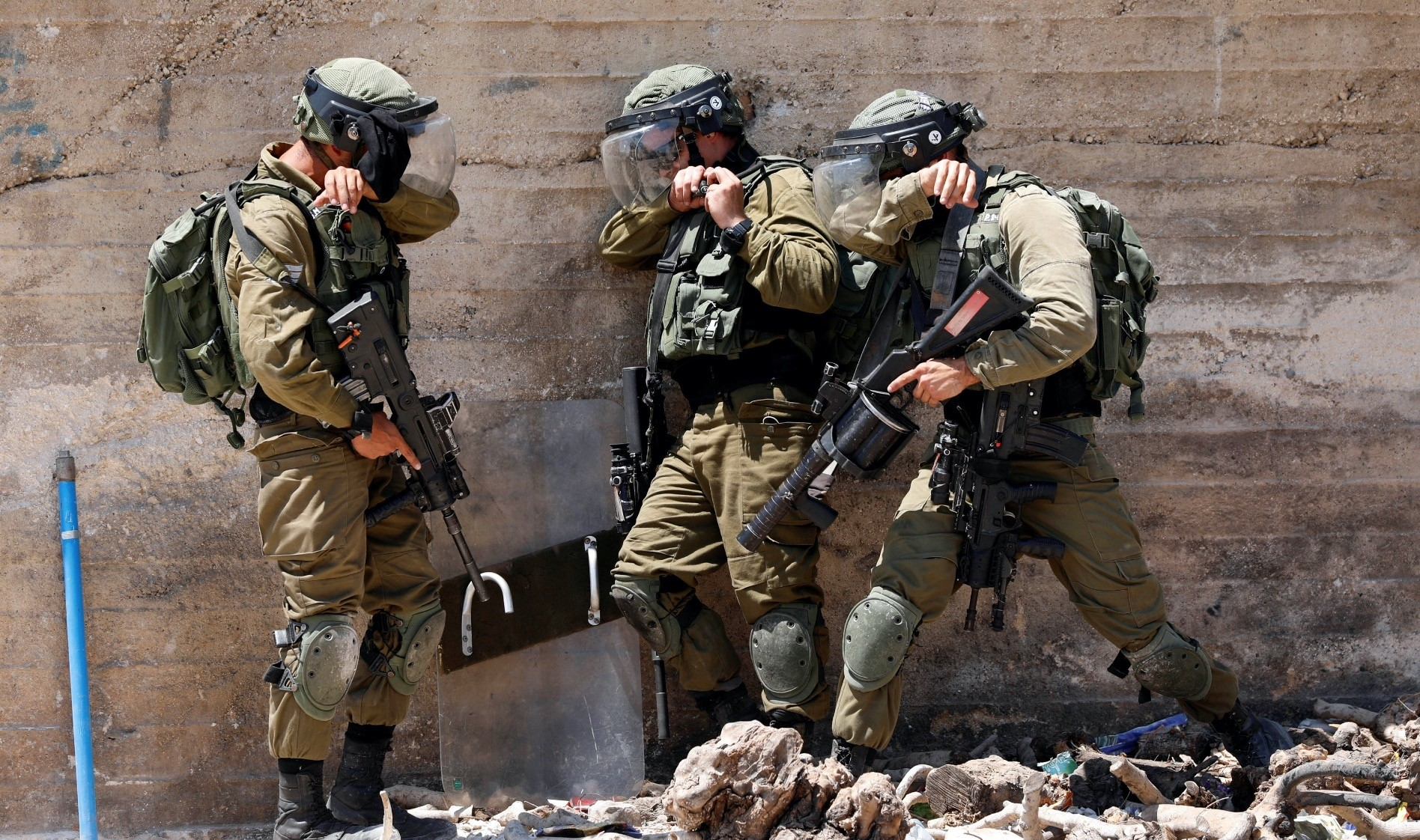 Israeli soldiers take cover during clashes with Palestinians in the occupied West Bank, Aug. 17.