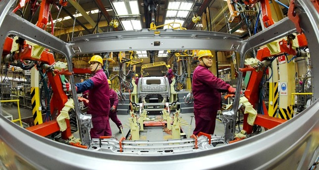 Employees work on a production line, manufacturing light trucks at a JAC Motors plant in Weifang, Shandong province, China, Nov. 30, 2018.
