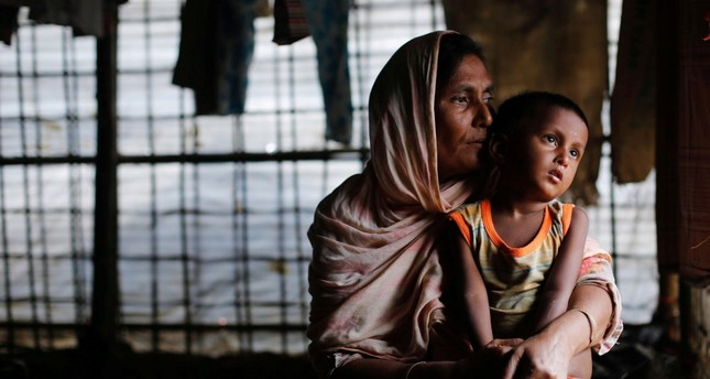 A Rohingya refugee woman waits for aid with her grandson inside their temporary shelter at a camp in Cox's Bazar, Bangladesh, Sept. 19.