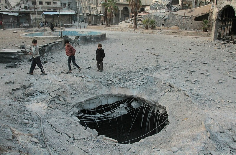 Children walk past a hole in the ground caused by strikes in the opposition-held town of Douma in Syria's eastern Ghouta region, Nov. 15, 2017. (AFP Photo)