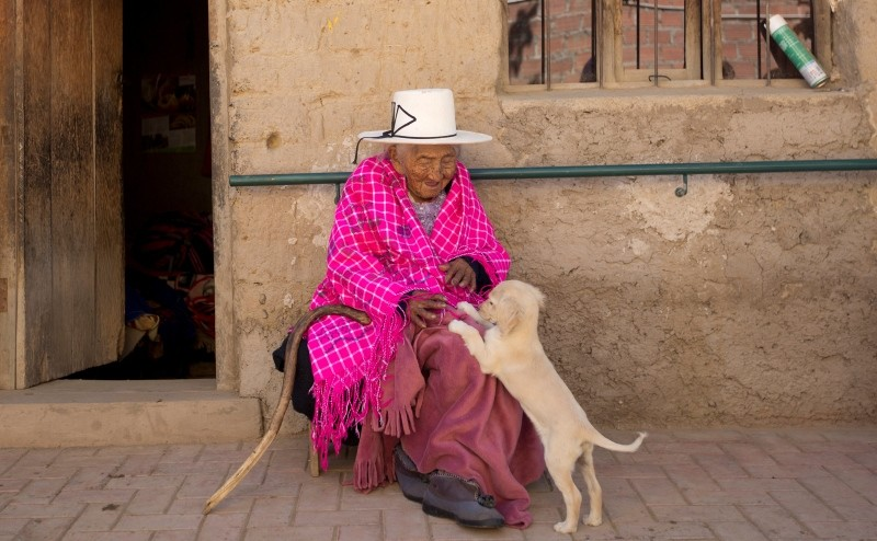In this Aug. 23, 2018 photo, 117-year-old Julia Flores Colque plays with ,Chiquita,, one of the family pet dogs, while sitting outside her home in Sacaba, Bolivia. (AP Photo)