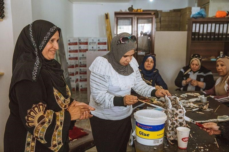 Syrian refugee Sameera al-Salam shows a colleague how to strengthen a paper handbag with glue at an upcycling workshop.