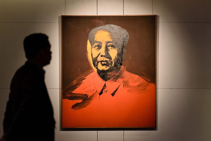 This file photo taken on March 17, 2017 shows a man walking past u2018Maou2019 by US artist Andy Warhol, 1973, an acrylic and silkscreen ink on canvas, during a pre-auction preview by Sotheby's in Hong Kong. (AFP Photo)