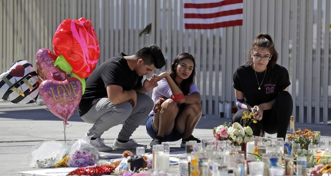 Roberto Lopez, from left, Briana Calderon and Cynthia Olvera, of Las Vegas, pause at a memorial site on Tuesday, Oct. 3, 2017 in Las Vegas. (AP Photo)