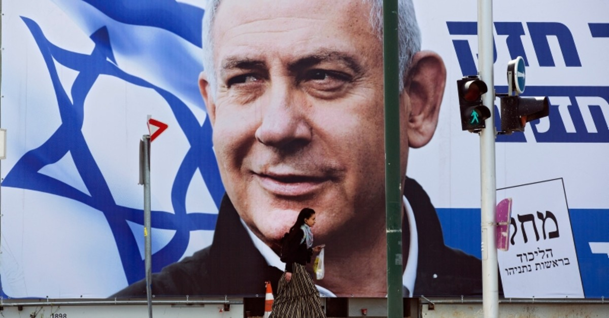 A woman walks by an election campaign billboard showing Israel's Prime Minister Benjamin Netanyahu, the Likud party leader, in Tel Aviv, Israel, Thursday, March 28, 2019.
