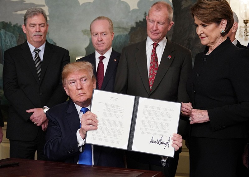 US President Donald Trump signs trade sanctions against China on March 22, 2018, in the Diplomatic Reception Room of the White House in Washington, DC, on March 22, 2018 (AFP Photo)