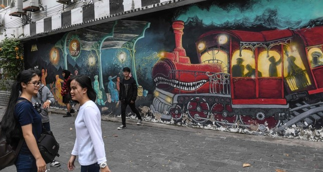 Visitors walking next to graffiti at 3A Station, a graffiti hub and street art area in Ho Chi Minh City. (AFP Photo)