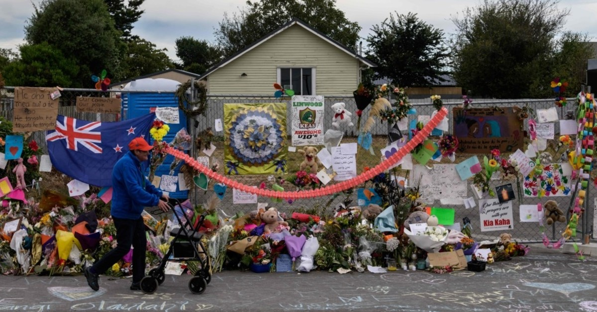 A man walks past flowers and tributes displayed in memory of the twin mosque massacre victims along the road outside the Linwood mosque (back C) in Christchurch, March 25, 2019.
