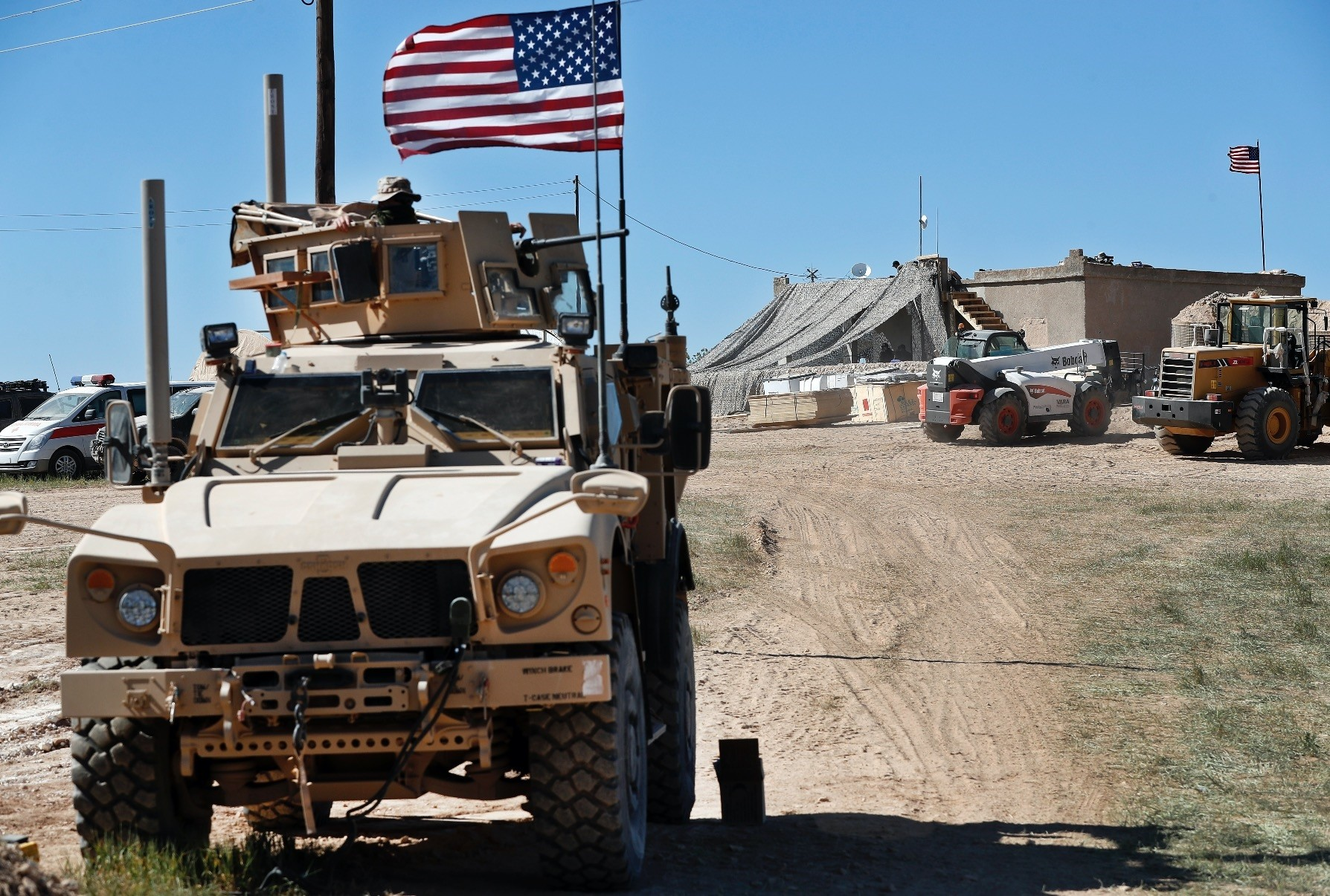 A U.S. soldier (L) sits on an armored vehicle at a newly installed position near the line where a Turkish-backed opposition group maintains the anti-terror offensive, Operation Olive Branch, against the U.S-backed YPG, Manbij, Syria, April 4.