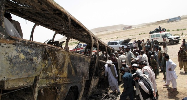 Afghan security officials survey the scene of a transport accident in Maiwand district of Helman province, Afghanistan, 26 April 2013 (EPA File Photo)