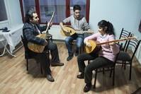 سليمان أكيجي معلم العزف على البزق/ يسار (الأناضول)