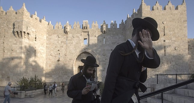 Ultra-Orthodox Jews and muslims passing at Damascus gate of the the old city of Jerusalem, 22 September 2016 (EPA Photo)