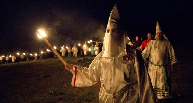 In this Saturday, April 23, 2016 photo, members of the Ku Klux Klan participate in cross burnings after a white pride rally in rural Paulding County near Cedar Town, Ga. (AP Photo)