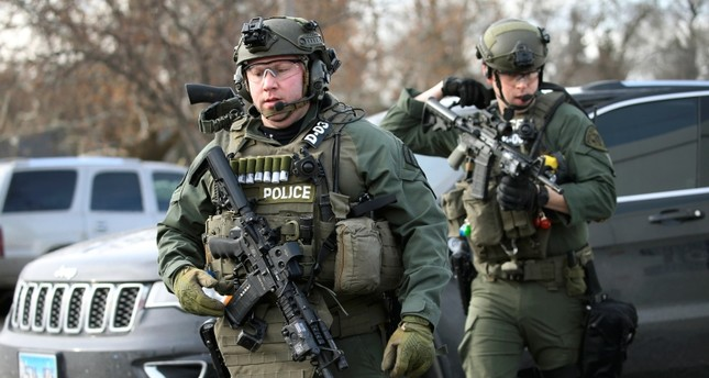 Police officers armed with rifles gather at the scene where an active shooter was reported in Aurora, Ill., Friday, Feb. 15, 2019 (AP Photo)