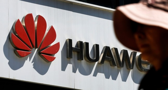 In this May 29, 2019, file photo, a woman walks by a Huawei retail store in Beijing. (AP Photo)