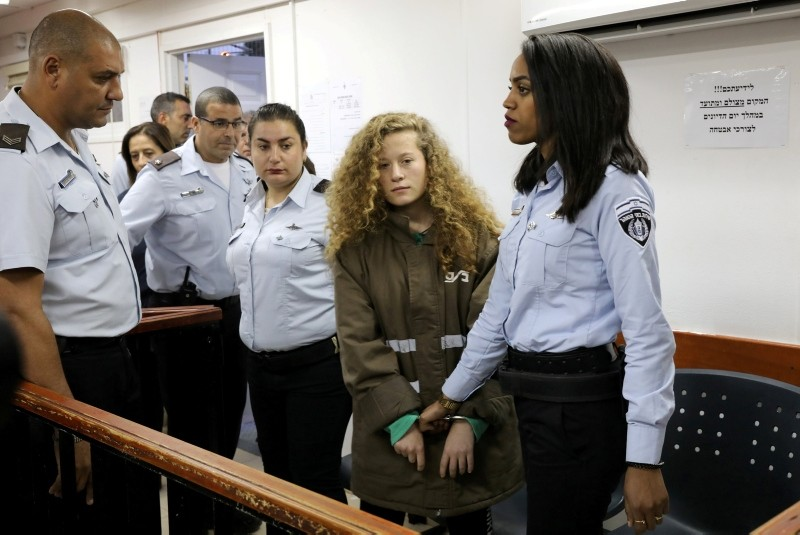 Palestinian teen Ahed Tamimi enters a military courtroom escorted by Israeli Prison Service personnel at Ofer Prison near the West Bank city of Ramallah, December 28, 2017. (Reuters Photo)