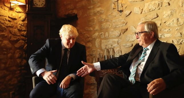 European Commission President Jean-Claude Juncker R reaches out to shake hands with British Prime Minister Boris Johnson prior to a meeting at a restaurant in Luxembourg, Sept. 16, 2019.