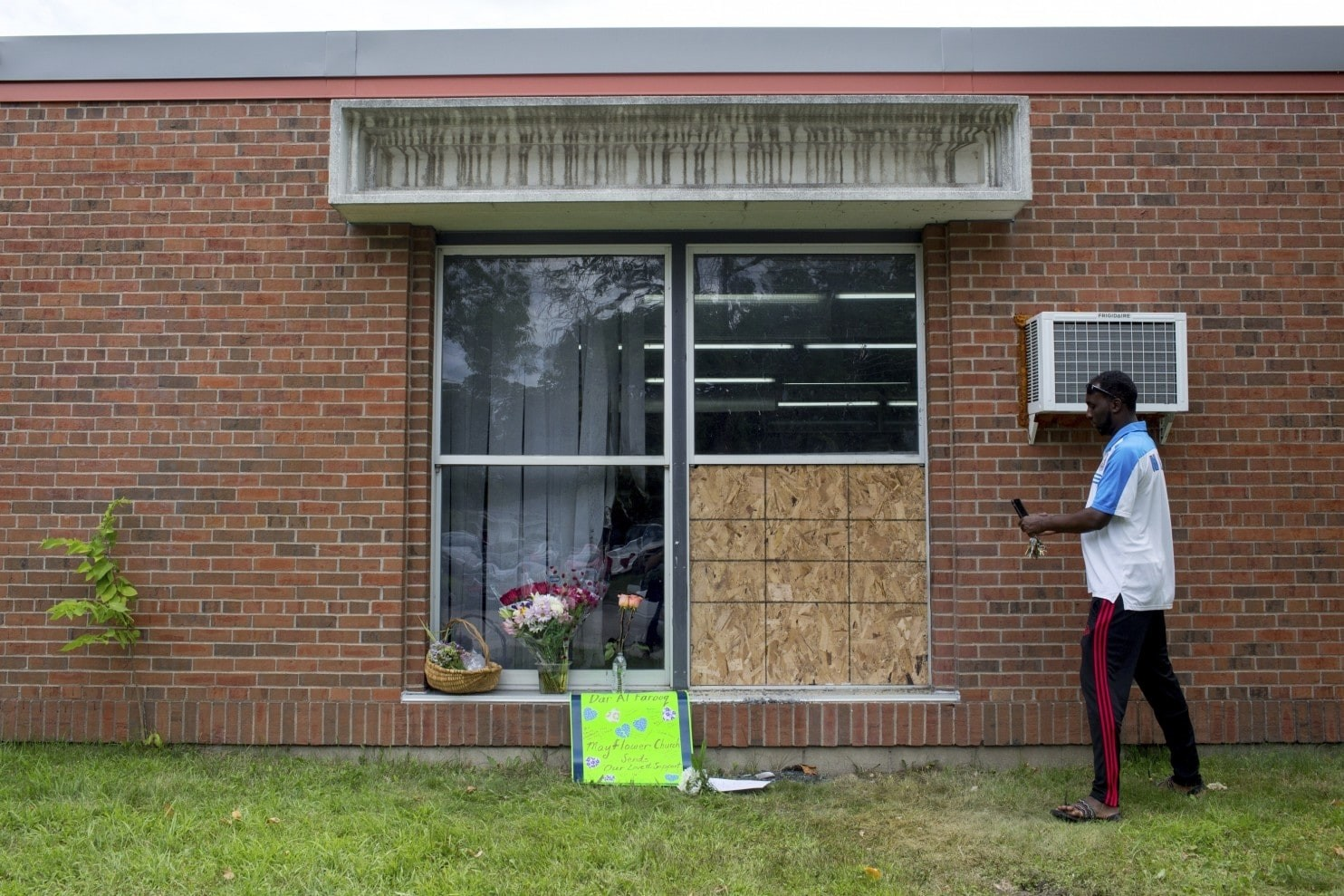 Abdul Mohamed photographs the damage outside of the Dar Al Farooq Islamic Center in Bloomington, Minnesota, Sunday, Aug. 6, 2017. (AP Photo)