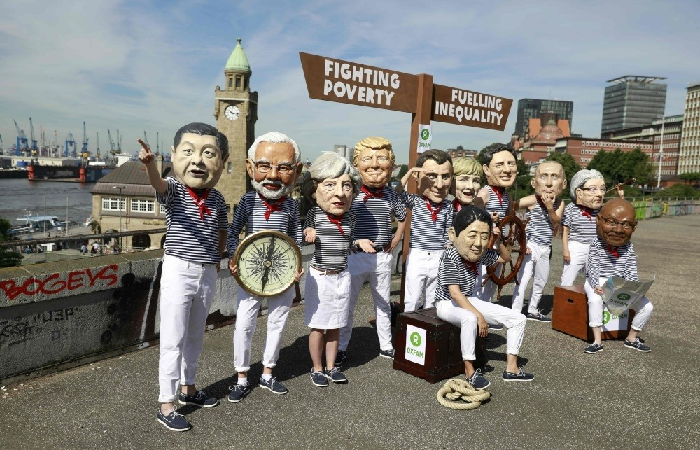 Activists wearing masks featuring the leaders of some G20 member countries during a protest against the G20 due to its lack of activity to fight global problems, July 6, Hamburg, where the G20 leaders will gather for a summit.