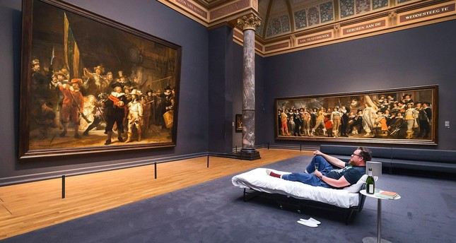 This handout picture released on June 2, 2017 by the Rijksmuseum of Amsterdam shows Stefan Kasper lying in a bed in front of the painting The Night Watch by Dutch painter Rembrandt at the Rijksmuseum of Amsterdam on June 1, 2017. (AFP Photo)