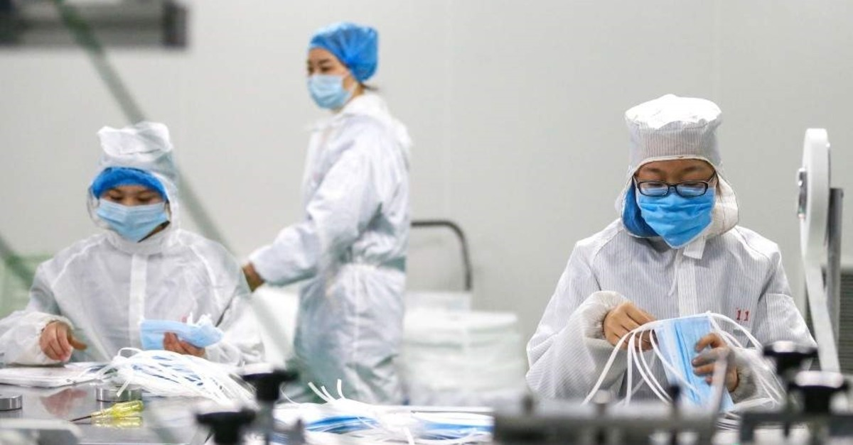 Workers produce face masks to prevent infection of a new virus at a factory in Qingdao, Shandong province, China, Feb. 6, 2020. (AFP Photo)