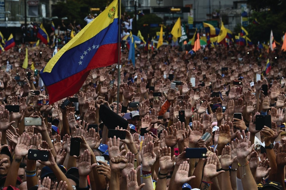 People raise their hands during a mass opposition rally against President Nicolas Maduro, in Caracas, Jan. 23.