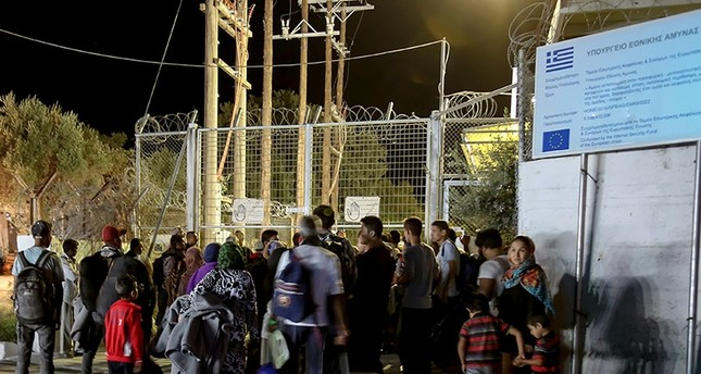 Refugees and migrants stand at the closed gate of the Moria migrant camp, after a fire at the facility, on the island of Lesbos, Greece, Sept. 19, 2016. Reuters Photo