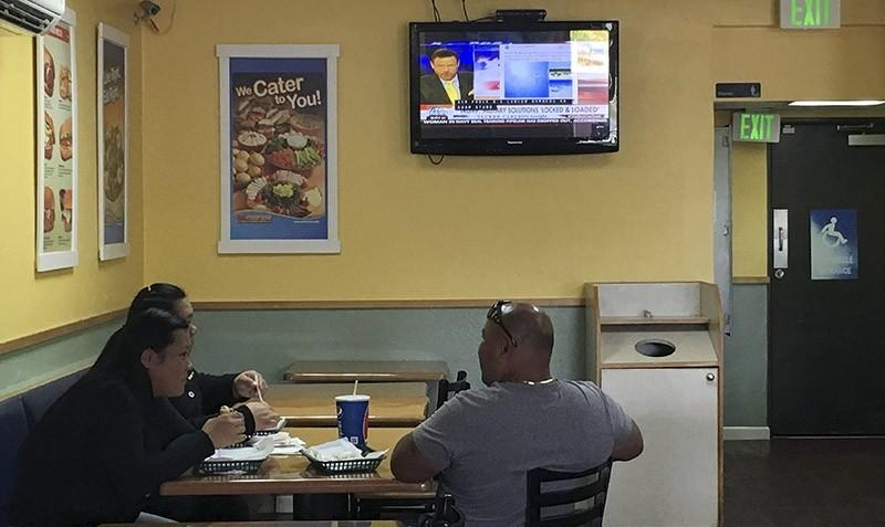 Residents watch TV news at a sandwich shop in Hagatna, Guam, Saturday, Aug. 12, 2017  (AP Photo)
