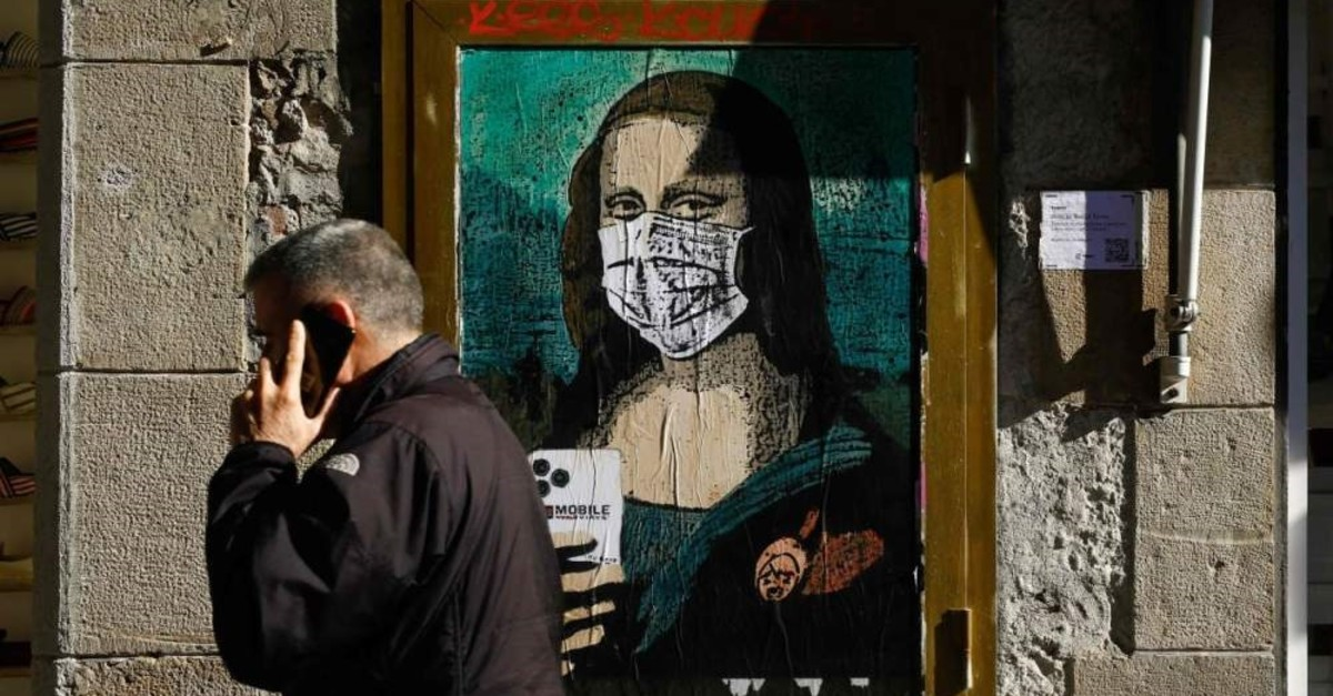 A man holding his mobile phone walks past a poster depicting Leonardo da Vinci's Mona Lisa wearing a protective facemask and holding a mobile phone reading ,Mobile World Virus,, Barcelona, Feb. 18, 2020. (AFP Photo)