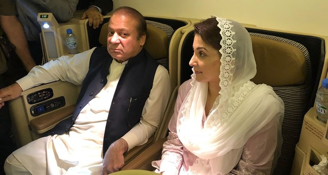 This handout photograph released by Pakistan Muslim League Nawaz PML-N party on July 14, 2018, show former prime minister Nawaz Sharif L and his daughter Maryam Nawaz siting on a plane after their arrival in Lahore. AFP Photo