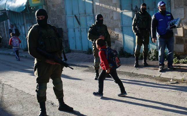Palestinian children walk past Israeli soldiers on their way to school in the West Bank city of Hebron, Feb. 12, 2019.