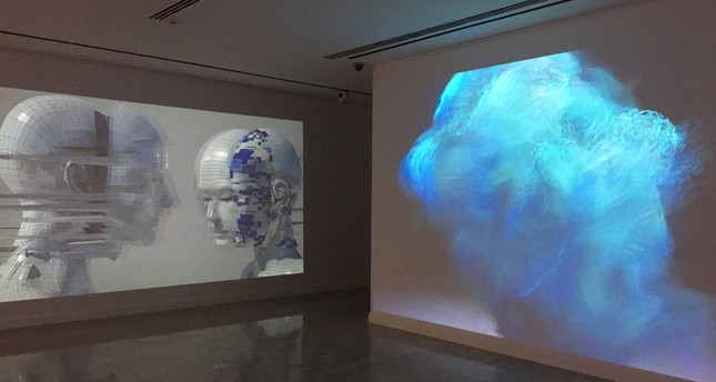 """Untitled Fur Suit"" by A Bill Miller plays at the center projection screen in tufts of soft and pacifying virtual textures with Elena Romenkova's ""Two 20001_1."""