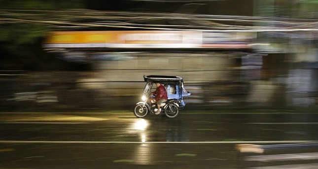 A man rides his tricycle as strong winds and rain from Typhoon Mangkhut batter Tuguegarao city, Cagayan province, northeastern Philippines on Saturday, Sept. 15, 2018. (AP Photo)