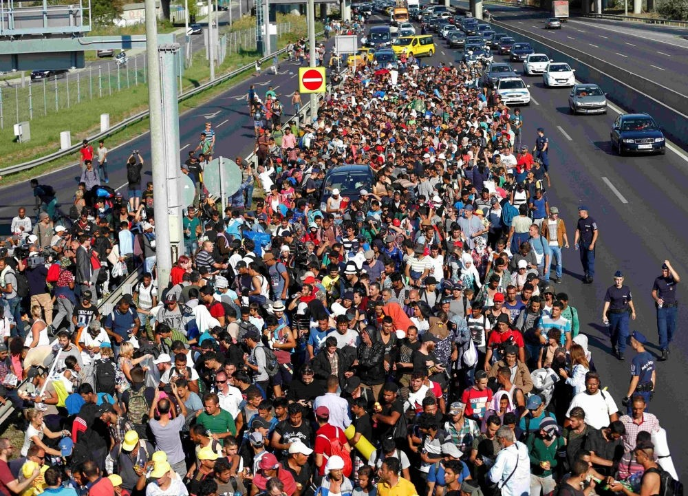Migrants march along the highway at the border with Austria, out of Budapest, Hungary.