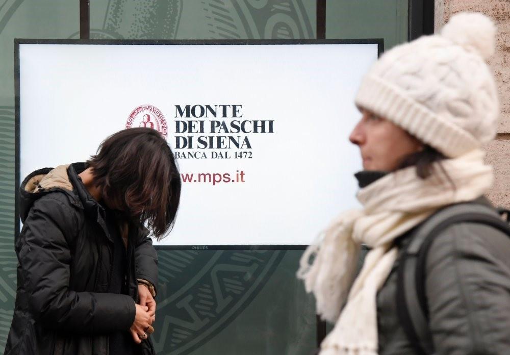 People walk past an office of Italian bank Monte Dei Paschi Di Siena.