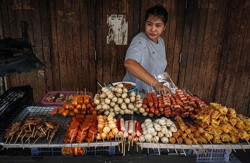 A woman arranges fried snacks on her street food cart the Pratunam district of Bangkok on April 18, 2017.